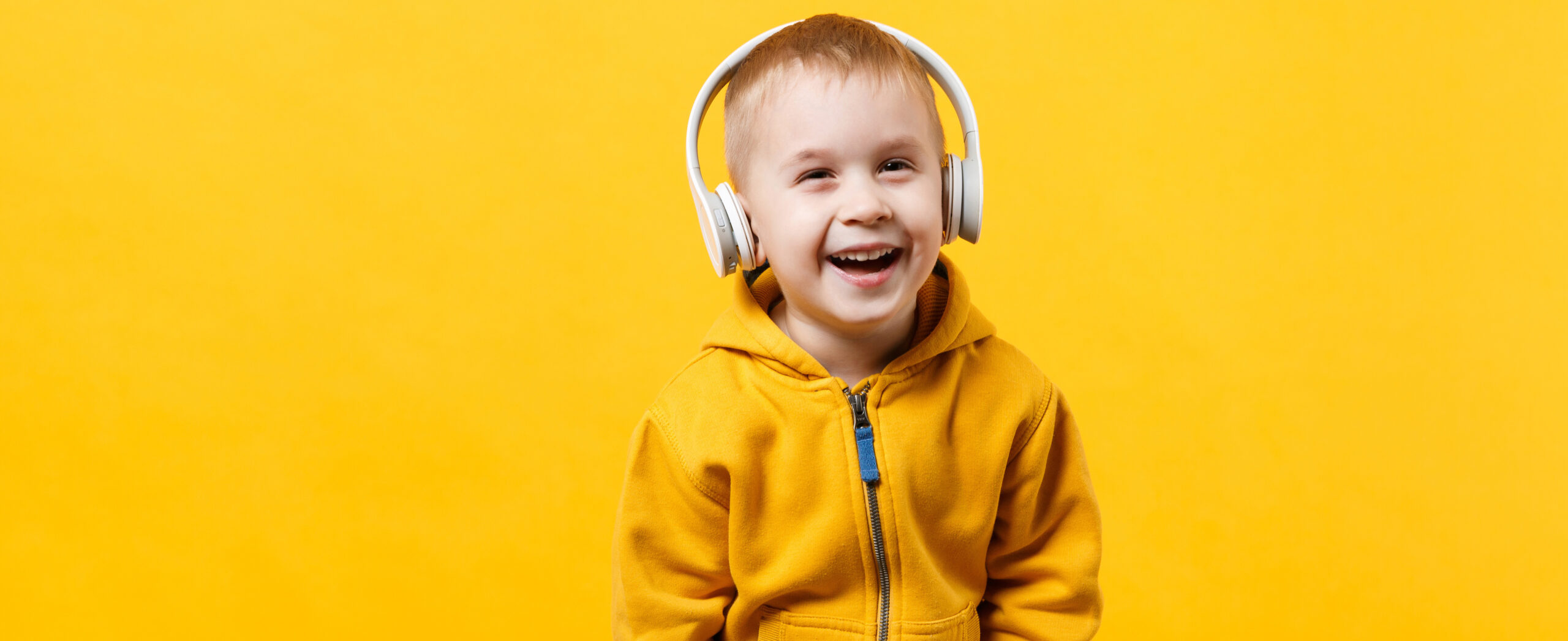 Little kid boy 3-4 years old wearing yellow clothes in headphones isolated on orange wall background, children studio portrait. People sincere emotions childhood lifestyle concept. Mock up copy space